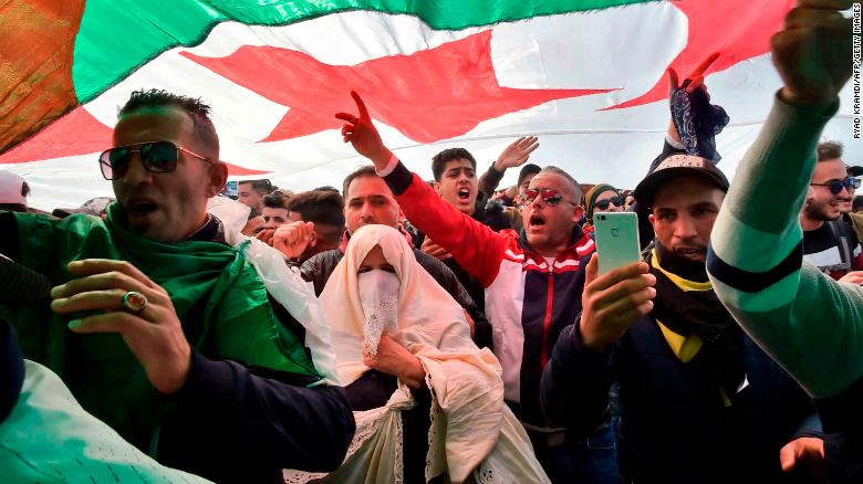 Algerians chant slogans under a national flag Friday in the capital.