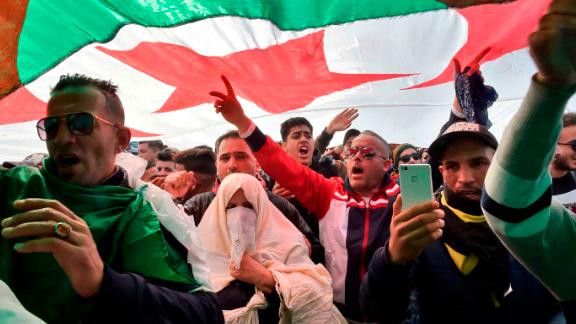 Algerians chant slogans under a national flag during a protest rally on Friday.