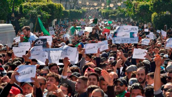 "Algerians march with protest sings reading ""peaceful"", and ""leave means leave"" in Arabic, during a rally against ailing President Abdelaziz Bouteflika's bid for a fifth term in power, in the capital Algiers on March 1, 2019. - The demonstrations came a week after tens of thousands of people rallied in the North African state against 81-year-old Bouteflika's decision to stand in the April 18 election. (Photo by RYAD KRAMDI / AFP)        (Photo credit should read RYAD KRAMDI/AFP/Getty Images)"