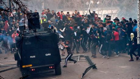 Protestors attempt to overturn a police van in Algiers on Friday.