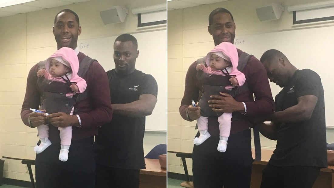 Wayne Hayer helps fasten his daughter Assata in a harness worn by his professor, Nathan Alexander. The professor offered to carry the baby during class so Hayer could take notes.