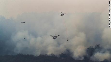 Helicopters drop water on a bushfire near Yiinnar in Gippsland, Australia, on Monday.