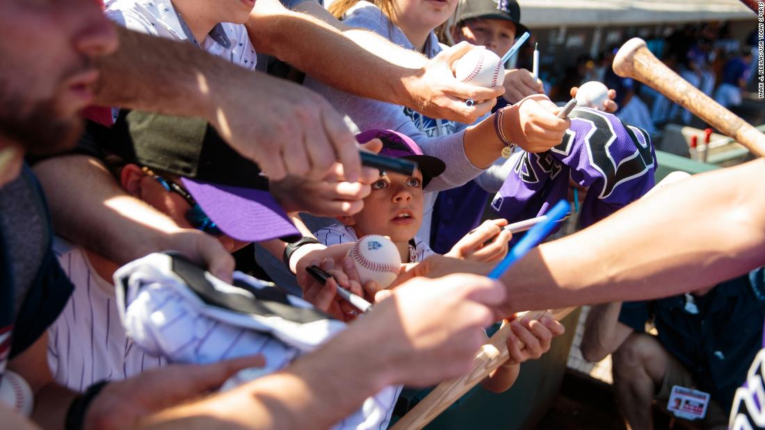 A young Colorado Rockies fan attempts to get an autograph prior to a spring training game between the Rockies and the Los Angeles Angels at Salt River Fields at Talking Stick on February 27, in Scottsdale, Arizona.