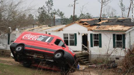 A van is upended in front of a damaged home in Lee County, Alabama, on Monday.