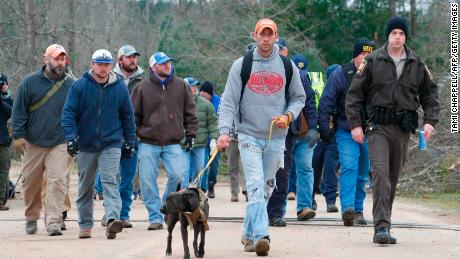 A search and rescue team walks past damage from a tornado in Alabama.