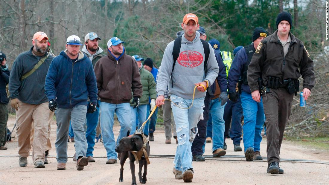 A search-and-rescue team walks past damage in Beauregard.