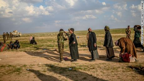 Men suspected of being Islamic State (IS) fighters are searched by members of the Kurdish-led Syrian Democratic Forces (SDF) after leaving the IS group's last holdout of Baghouz in Syria's northern Deir Ezzor province, on February 22, 2019. (Photo by Bulent KILIC / AFP)        (Photo credit should read BULENT KILIC/AFP/Getty Images)