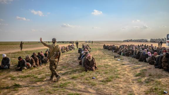 Men suspected of being ISIS fighters wait to be searched by the Kurdish-led Syrian Democratic Forces after leaving Baghouz last month.