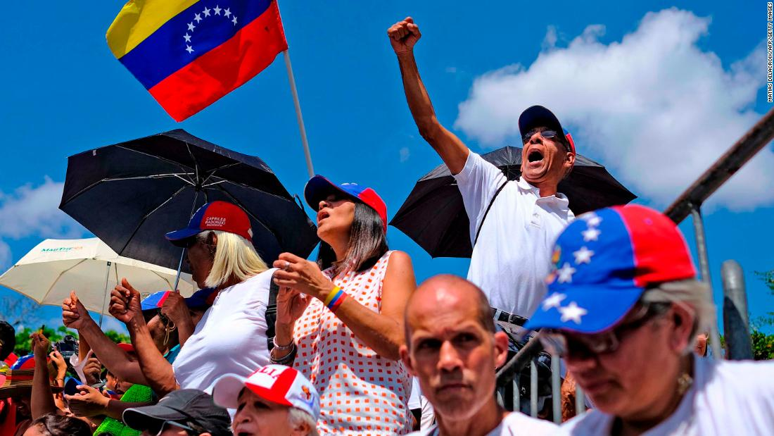 Supporters of Venezuelan opposition leader Juan Guaido wave a Venezuelan flag as they wait for him to make an appearance in the country's capital of Caracas on Monday, March 4.