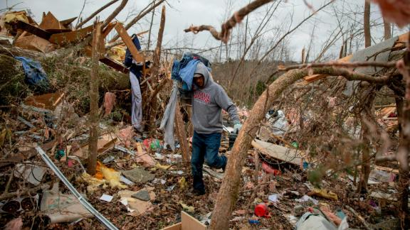 Danny Allen helps recover belongings while sifting through the debris of a friend