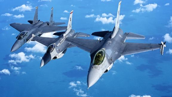 Two Singaporean F-16s fly in formation with an F-15 in 2017. The country's defense minister says the F-16s will be obsolete by 2030.