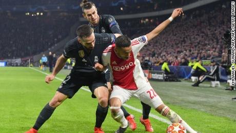Ajax midfielder Hakim Ziyech (R) fights for the ball with Real Madrid's Spanish defender Dani Carvajal (L) and Real Madrid's Welsh forward Gareth Bale.