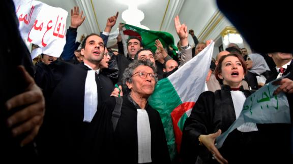 """Algerian lawyers protest on February 25, holding up placards with slogans in Arabic that read: """"The lawyers are with the people."""""""