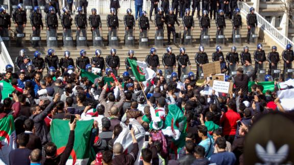 Algerians shout slogans and raise signs and national flags as they protest outside the city hall in the northern coastal city of Oran, about 410 kilometers west of the capital Algiers.