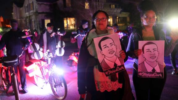 Protesters march through the streets as they demonstrate against a decision not to charge the Sacramento police officers who shot and killed Stephon Clark.