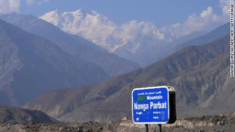 In this photograph taken on August 7, 2014 a sign points towards a view of Nanga Parbat (background), the killer mountain on Karakoram Highway in Pakistan's nothern area of Gilgit.