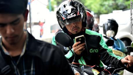 A GrabBike rider uses his mobile phone in Jakarta in 2017.