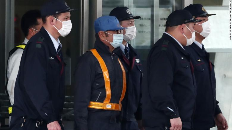 Carlos Ghosn, wearing a light blue cap, left a Tokyo detention center on Wednesday after more than 100 days in detention.