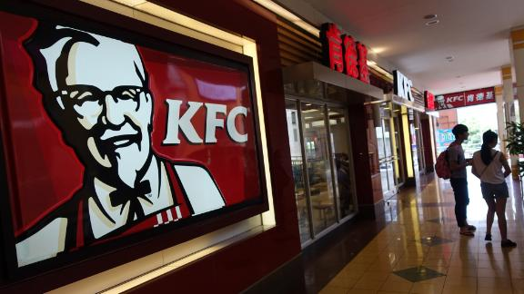 Two people walk past a KFC fast food restaurant (L) in Shanghai on July 23, 2014. Chinese police on July 23 detained five people from a unit of US food supplier OSI Group, officers said, in a case involving expired meat sold to fast food giants including McDonald's and KFC.    AFP PHOTO / JOHANNES EISELE        (Photo credit should read JOHANNES EISELE/AFP/Getty Images)