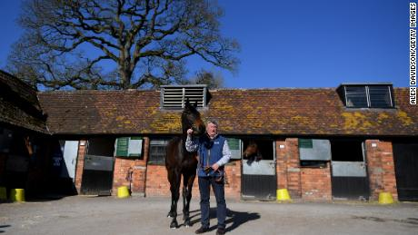 Trainer Paul Nicholls poses with Clan Des Obeaux at his Manor Farm Stables in Somerset, England.