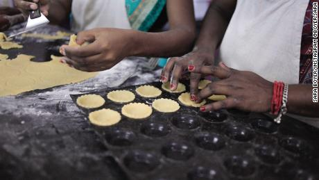 Bakery staff assemble pie shells for mini-chocolate tarts.