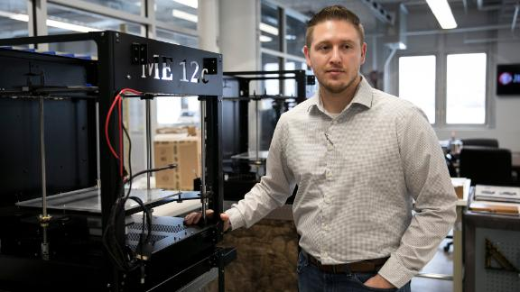 Zac DiVencenzo, COO of Juggerbot 3D, stands next to a 3D printer in Youngstown, OH on March 6, 2019.