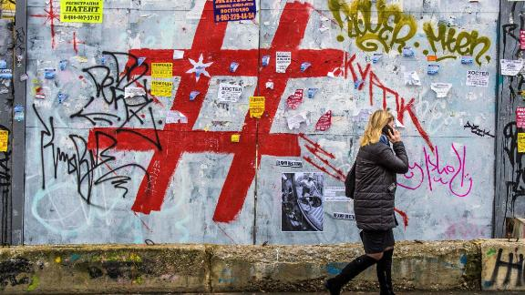 A woman walks past a graffiti covered wall with a giant hashtag sign near Moscow's Kursky railway station on November 17, 2017.