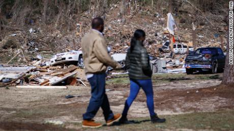 Krystal Stenson-Garrett walks with her husband, Shaun, through the wreckage where her family's homes used to be.
