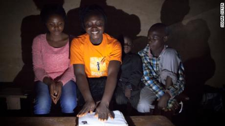 Nanbet Magdalene reads the bible to her children at night by solar light.