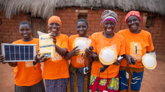 Solar Sister entrepreneurs hold up the renewable energy products they are selling.