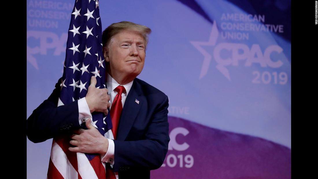 "US President Donald Trump hugs an American flag at the <a href=""https://www.cnn.com/2019/03/02/politics/trump-cpac-speech/index.html"" target=""_blank"">Conservative Political Action Conference</a> on Saturday, March 2."