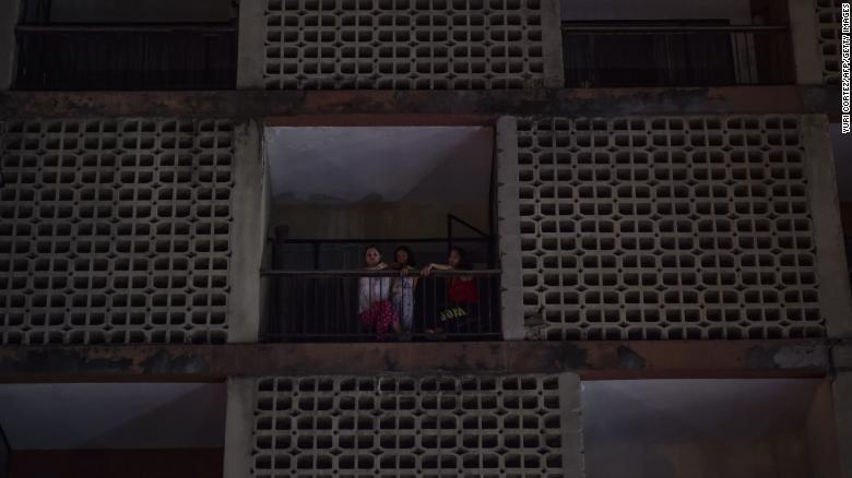 Women look from an apartment building during a power cut in Caracas.