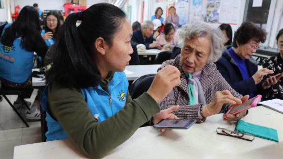A See Young volunteer explains how to send full-size pictures on WeChat to her retiree student.