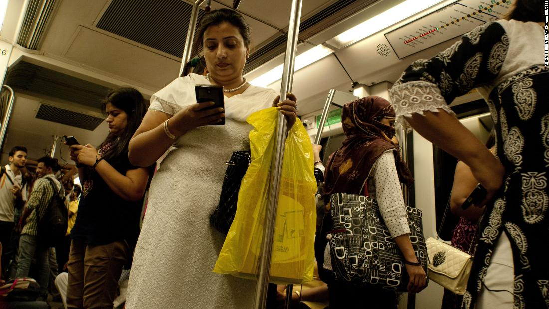 Indian women use their smartphones as they travel in the carriage reserved for women on the metro in New Delhi on July 3, 2015.