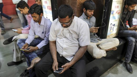 Passengers using smartphones at the central railway station in Mumbai.