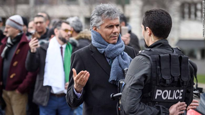Nekkaz (L) argues with a police officer during protests outside the Geneva University Hospitals.