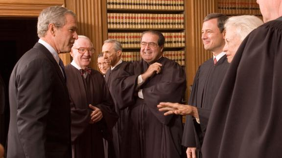 Bush enjoys a light moment with Roberts and other Supreme Court justices on Roberts