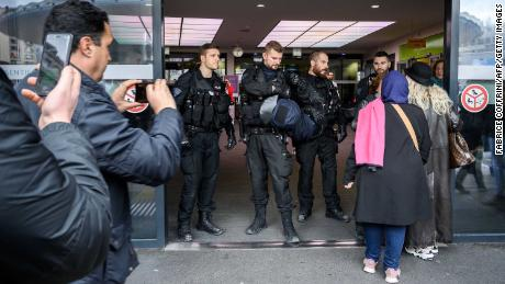 Police officers stand guard to prevent Algerian protesters from entering the Geneva University Hospitals.