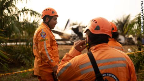 Members of the Colombian civil defense work on which a plane crashed