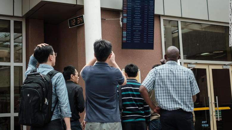 A Chinese group looks at the arrival flight schedule at Nairobi airport in Kenya on Sunday.
