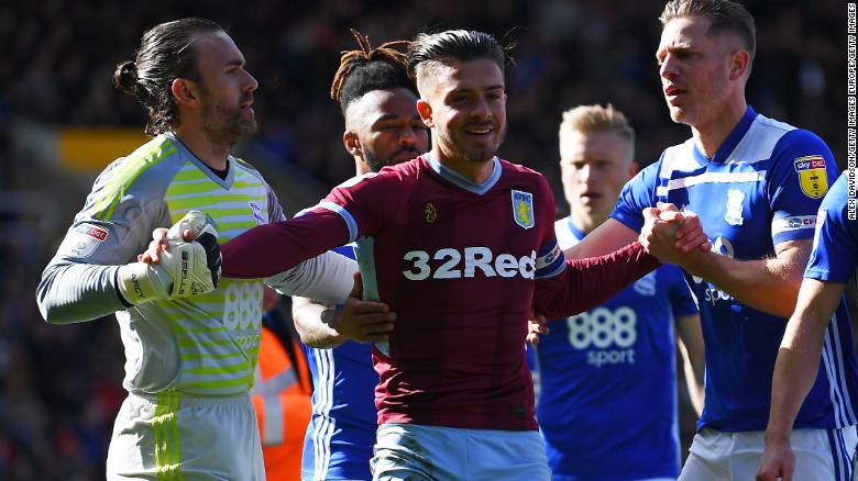 Jack Grealish is helped up after being struck by a fan.