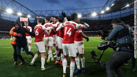 A fan runs onto the pitch as Arsenal celebrate its second goal.