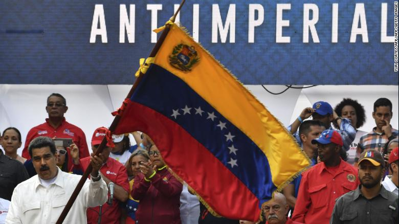 Maduro waves a Venezuelan flag at the rally at the Miraflores Presidential Palace in Caracas.