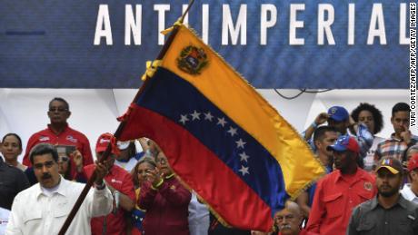 Maduro waves a Venezuelan flag at the rally at Miraflores presidential palace in Caracas.