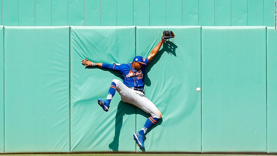 Keon Broxton of the New York Mets crashes into the wall attempting to catch a fly ball during the sixth inning of a Grapefruit League spring training game against the Boston Red Sox on March 9, in Fort Myers, Florida.