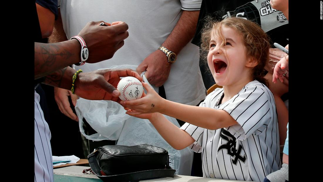Six-year-old Joan Stiltner receives an autographed baseball from Chicago White Sox left fielder Joel Booker before the team's spring training game against the Milwaukee Brewers on Thursday, March 7, in Glendale, Arizona.