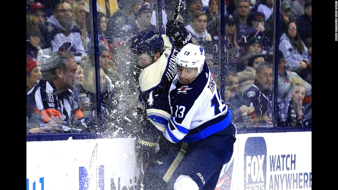 Columbus Blue Jackets defenseman Scott Harrington is checked into the glass by Winnipeg Jets left wing Brandon Tanev during the third period of an NHL game at Nationwide Arena on Sunday, March 3.