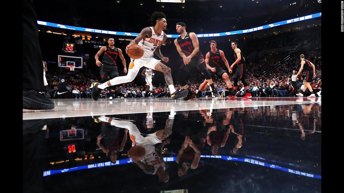 Kelly Oubre Jr. of the Phoenix Suns attempts to dribble past Seth Curry of the Portland Trail Blazers during the fourth quarter of an NBA game at the Moda Center on Saturday, March 9, in Portland, Oregon.