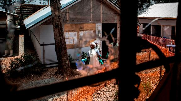 TOPSHOT - Health workers are seen through a bullet hole left in the window of an Ebola treatment centre, which was attacked in the early hours of the morning on March 9, 2019 in Butembo. - Armed men on March 9 attacked an Ebola treatment centre in the east of the Democratic Republic of Congo, killing a policeman and wounding a health worker, the authorities said. Suspected Mai-Mai rebels have attacked the Butembo ETC twice in the last two weeks. (Photo by JOHN WESSELS / AFP)        (Photo credit should read JOHN WESSELS/AFP/Getty Images)