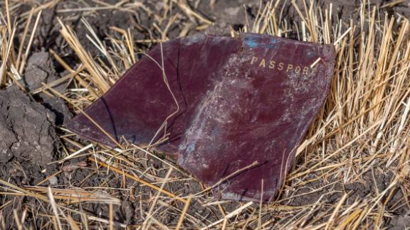 A passport lies on the ground at the scene of the crash.